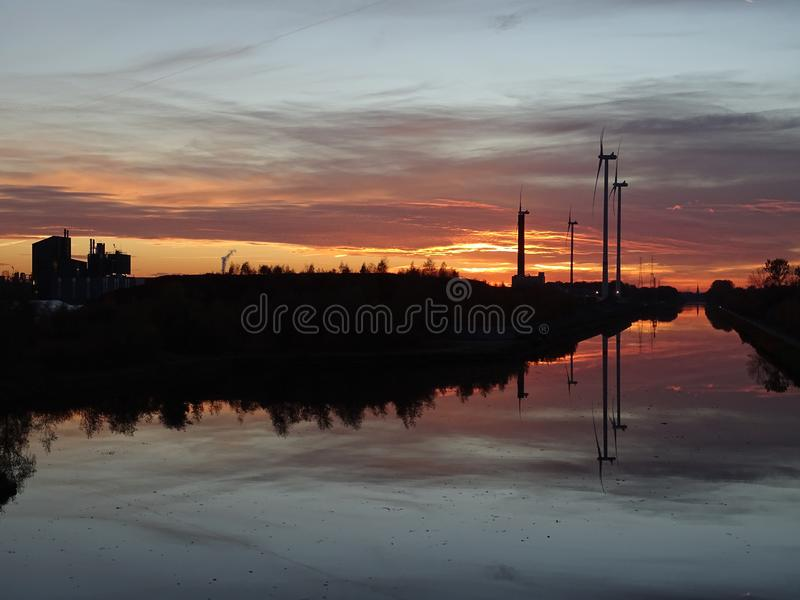 Windmills at sunset near the canal. And refections in the water, Industrial building on the left royalty free stock image