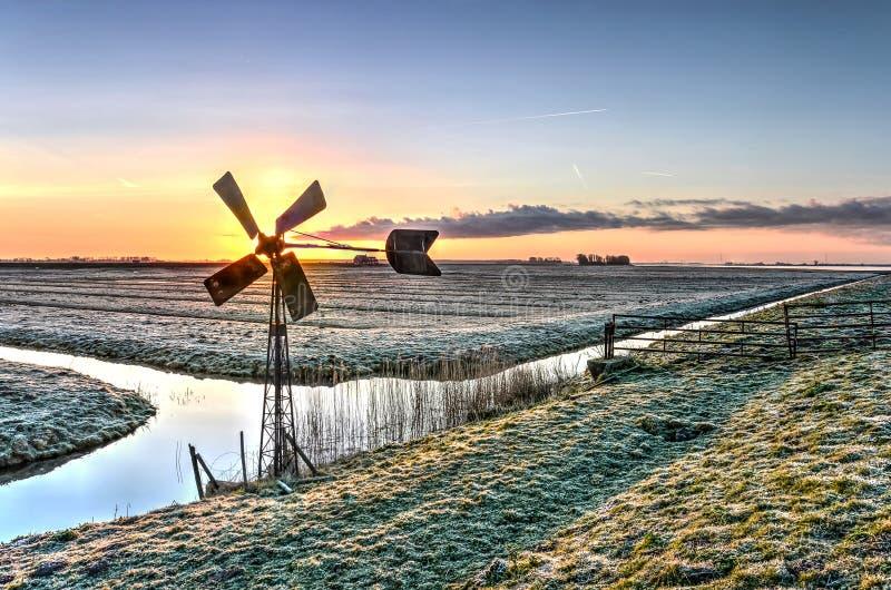 Windmolen bij zonsopgang stock afbeeldingen