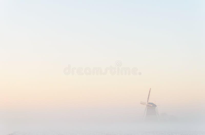 Windmolen in de mist stock foto's