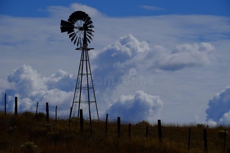 Windmolen op Helling in Platteland Landelijk Amerika met Hemel en C stock afbeelding