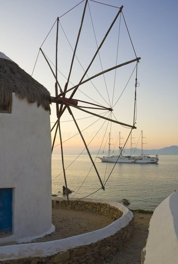 Windmolen tegen zonsondergang en cruiseschip stock foto