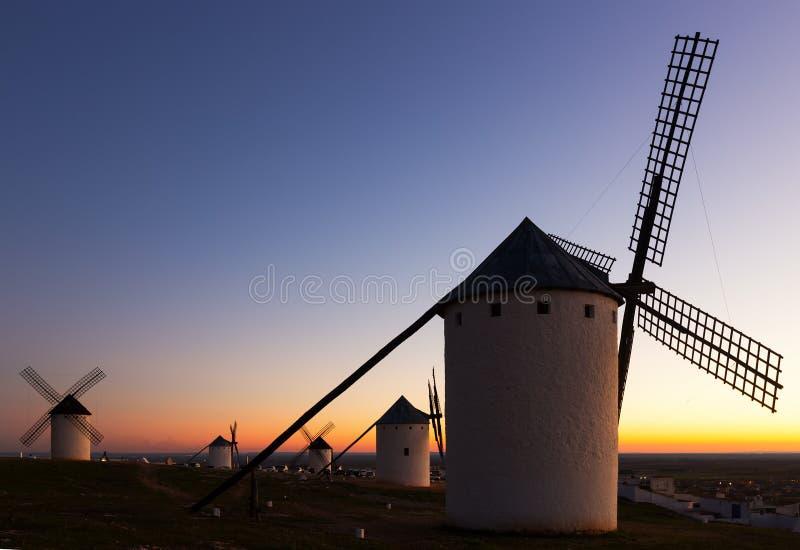 Windmolens bij gebied in schemer royalty-vrije stock afbeelding