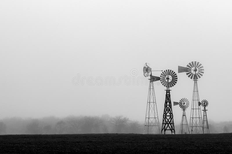 Windmolens in de mist royalty-vrije stock afbeelding