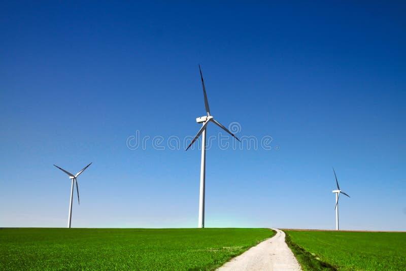 Windmolens op het groene gras stock afbeeldingen