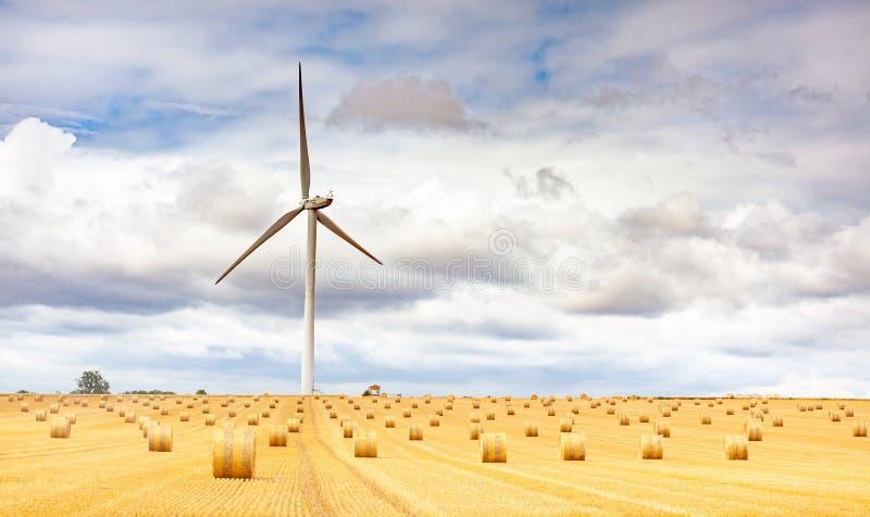 Windmolenturbine in een landbouwlandschap met akkers en grasland royalty-vrije stock afbeelding