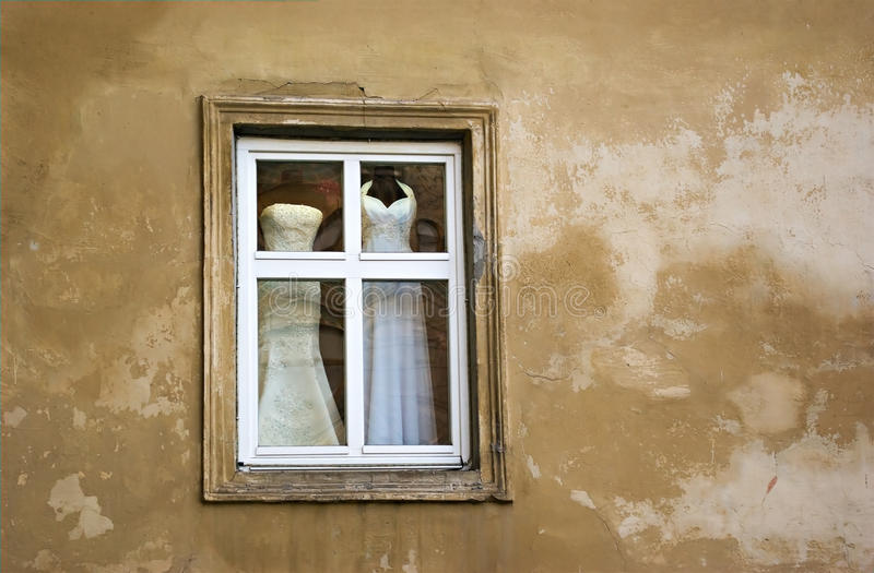 The window. Wedding dresses in the window of the old house royalty free stock photos