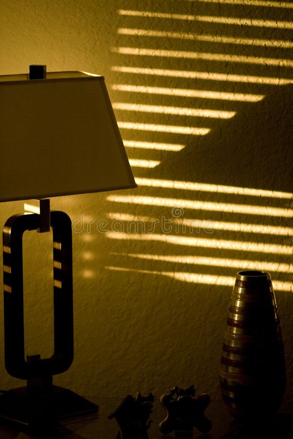 Sun Shining Through Window Blinds. Dark room with stripes of sunshine pattern on the wall. Sun is shining in through window blinds royalty free stock photos