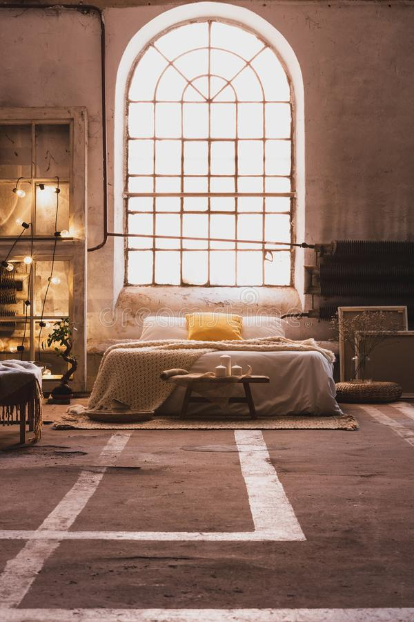Window above bed in spacious industrial bedroom. Interior with lights and wooden chair with blanket. Real photo royalty free stock photo