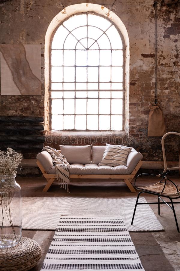 Window above grey wooden settee in spacious living room interior with armchair. And rug. Real photo stock photos