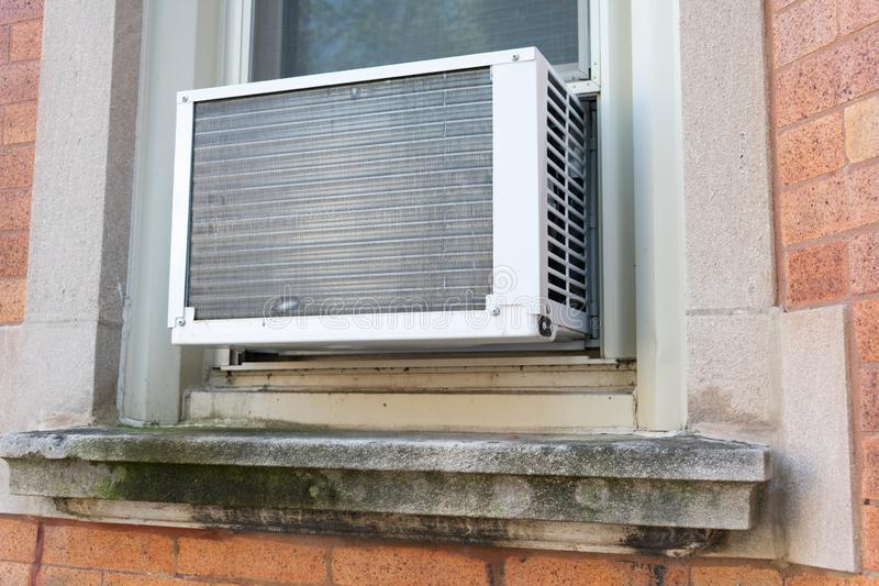 Window Air Conditioning Unit seen from Outside on a Brick Urban Building. A small and simple window air conditioning unit seen from the outside on a brick royalty free stock image