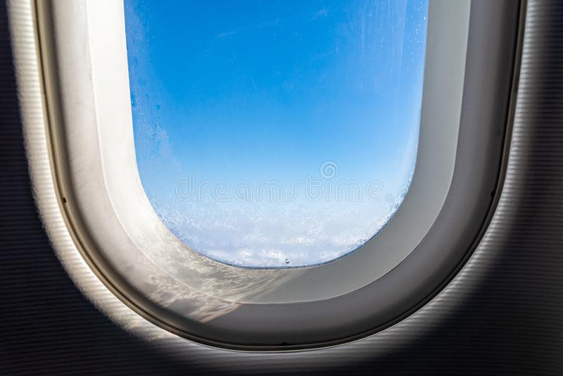 The window of the airplane. A view of porthole window on board an airbus for your travel concept or passenger air transportation. Clouds, aerial, aircraft royalty free stock photography