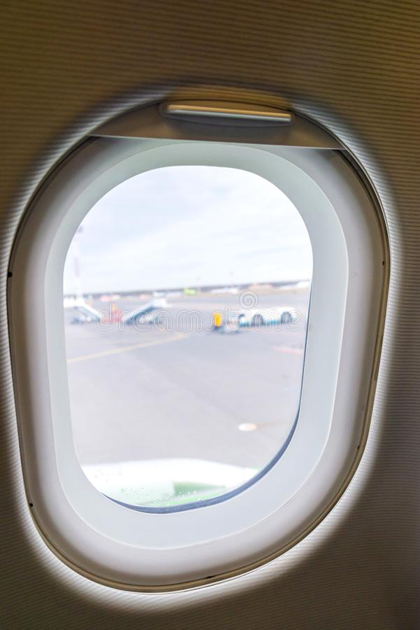 The window of the airplane. A view of porthole window on board an airbus for your travel concept or passenger air transportation. Clouds, aerial, aircraft stock images