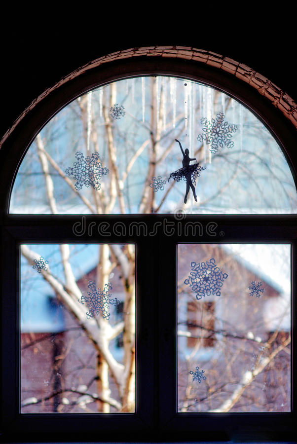 Window with art one sunny winter day. Window with snowflakes and ballerina in an winter day royalty free stock images