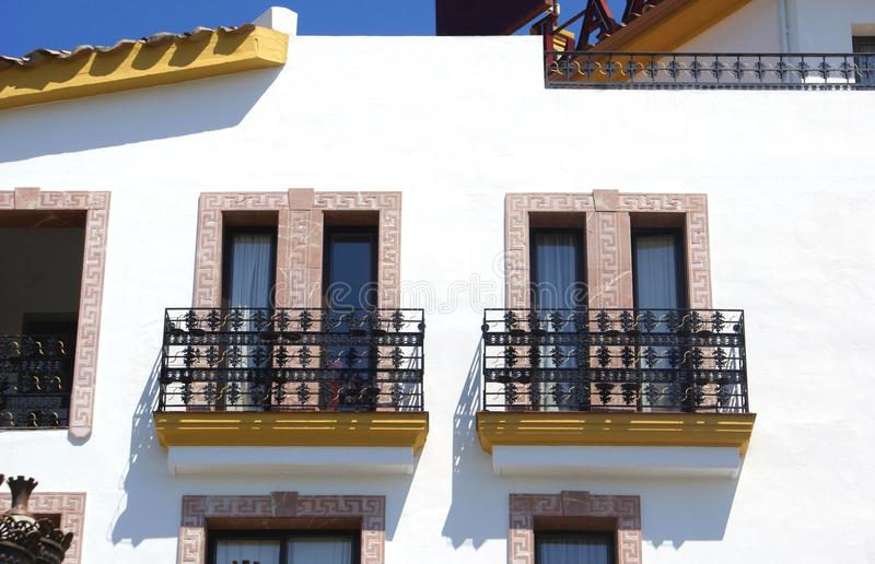 Window balconies. Details or closeup to a Spanish facade with window balconies royalty free stock image