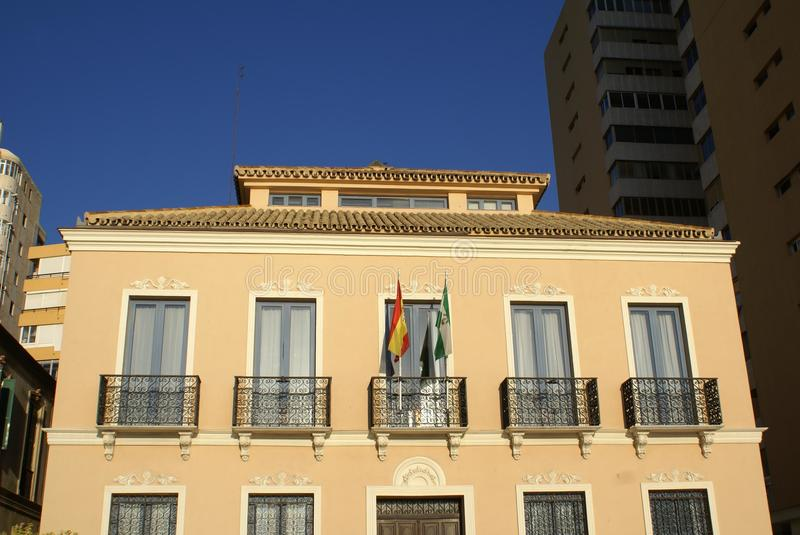 Window balconies with a Spanish flag. Outdoor urban view of a facade with arched window balconies and flags royalty free stock photo