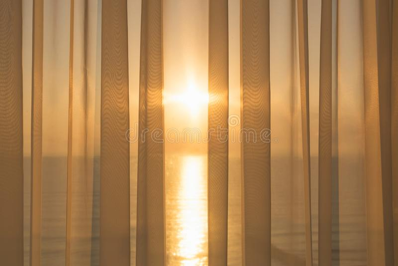 Window of a balcony with transparent curtains and view of morning sun and sea. Concept stock photo