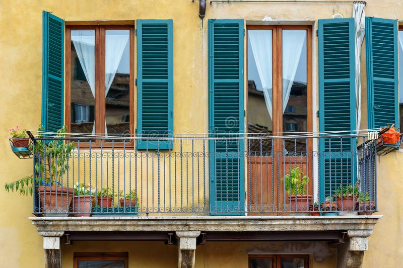 Window and balcony with wooden shutters of old house in Siena. Italy. Traditional window and balcony with wooden shutters of old house in Siena. Italy royalty free stock image