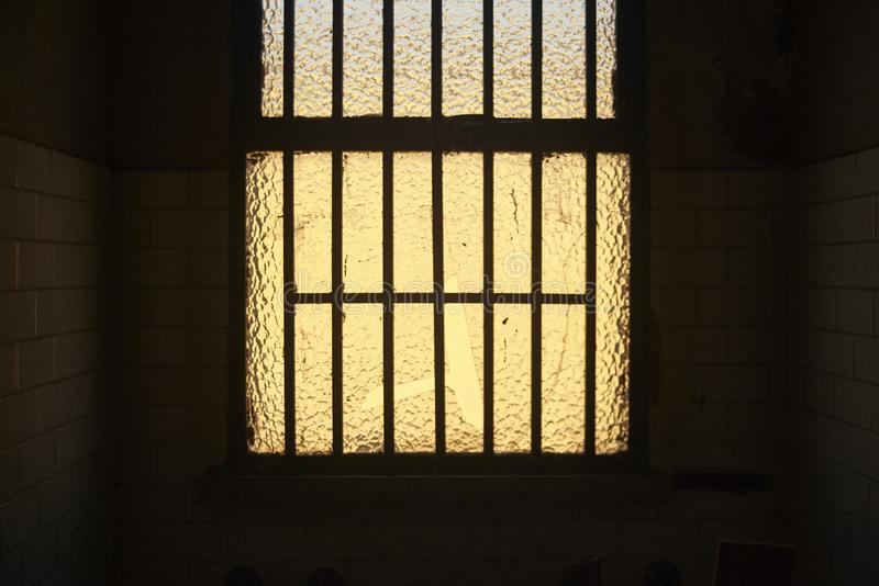 Window with bars of an abandoned building. Illuminated by the sun behind her is the central point of a dark room stock image