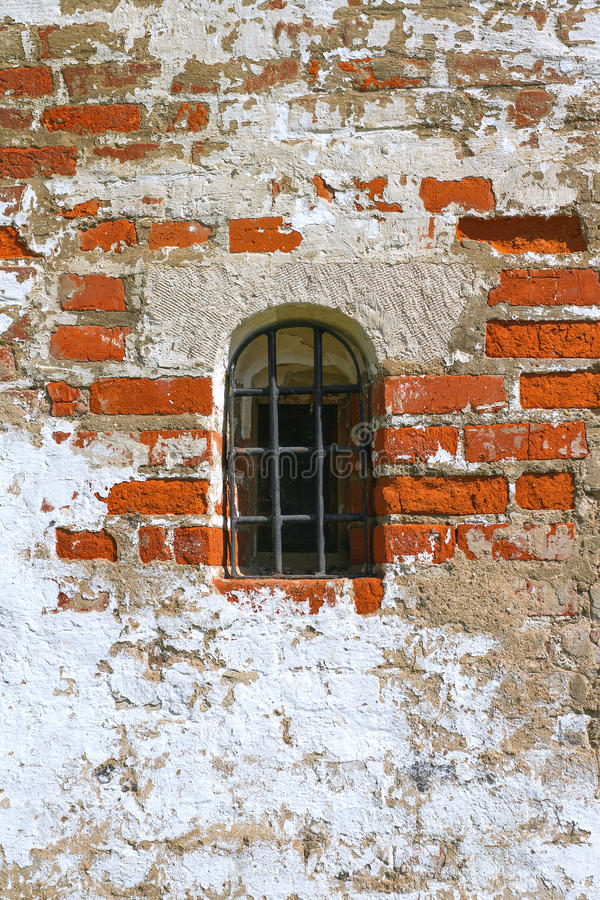 Window with bars. Window with iron bars in the old brick wall. Texture, background stock image