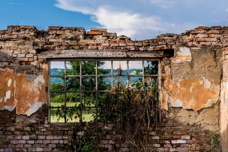Window with bars of an old ruin house near the forest and meadow in nature. View from a window with bars of an old ruin house near the forest and meadow in stock image