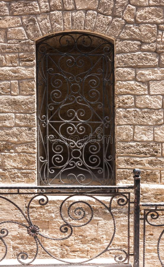 Window with bars in the wall of the old building. Icheri Sheher. Baku, Azerbaijan. 2018. Window with bars in the wall of the old building. Icheri Sheher. Baku stock image