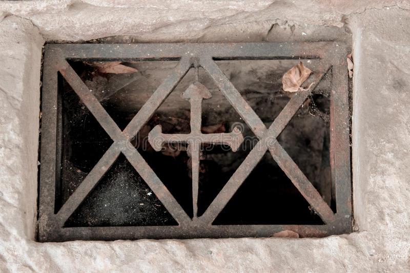 The window in the basement with a cross in metal frame with cobwebs in the corners, metal, rusty, scratched, dirty, dark bottom. The window in the basement with royalty free stock photography