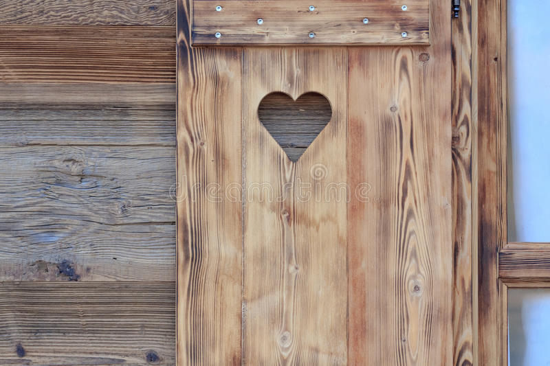 Window blind of a wooden hut with a heart shaped hole. Window blind of a wooden hut with heart shaped hole royalty free stock image