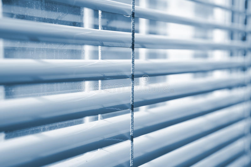 Window blinds. Window venitian plastic blinds in a shade of blue royalty free stock photos