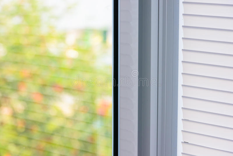 Window blinds. Closed plastic blinds on the window with the reflection in the glass stock images