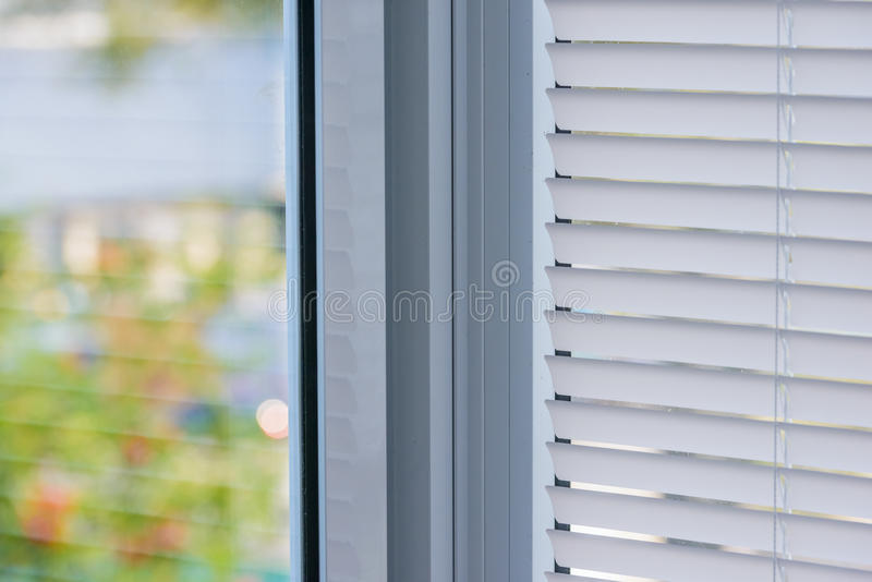 Window blinds. Closed plastic blinds on the window with the reflection in the glass royalty free stock photos