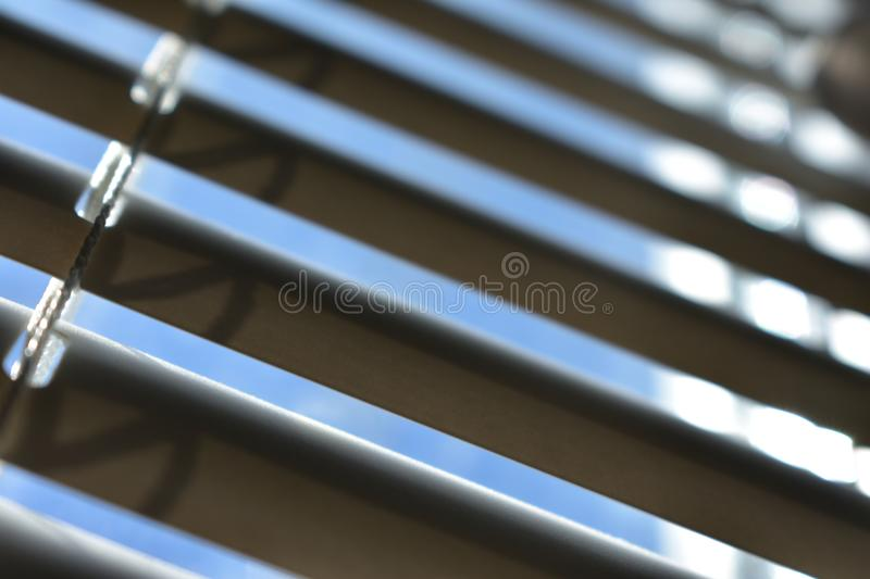 Window blinds, half open. You will see the blue sky and part of the window. Small depth of field. There`s room for your text. The texture of the louver which stock photography