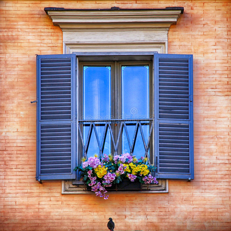 Window with blue shutters and flowers. Beautiful window with blue shutters and flowers in hanging flower pots, square image royalty free stock images