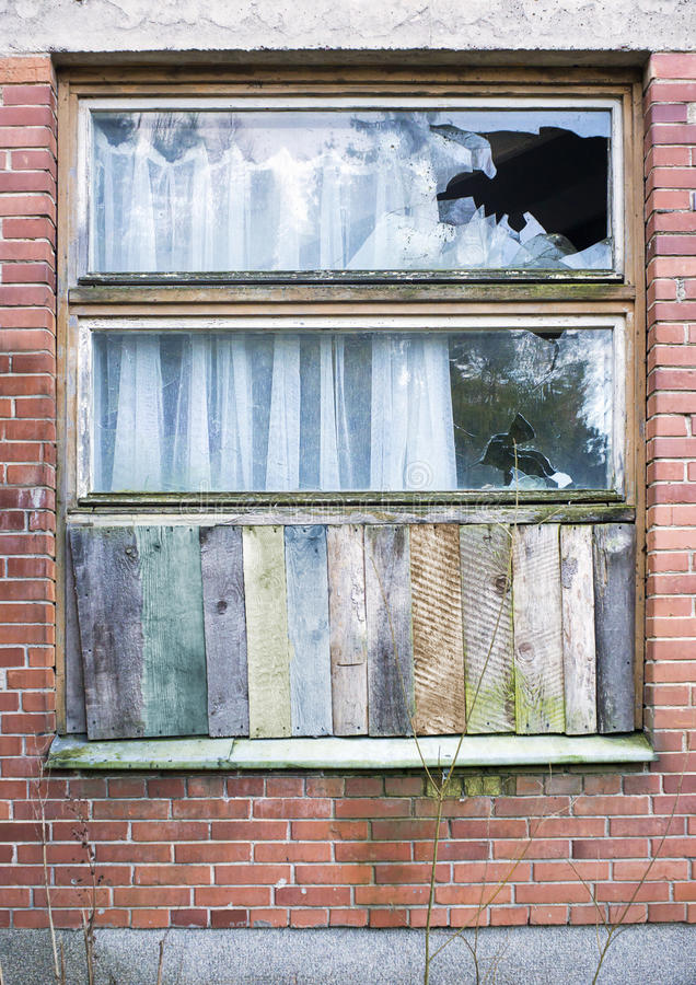 Window boarded up by wooden panels in an old red brick house. With beat all glass royalty free stock photography