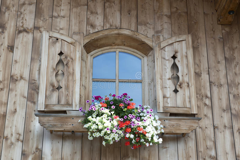 Window with blooming flowers in Austria. Window with blooming flowers on wooden hut in Austria royalty free stock photos