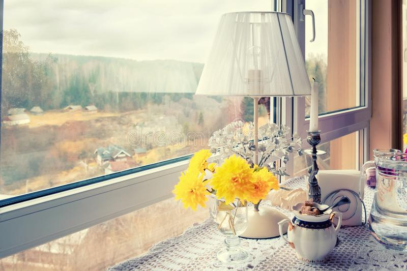 The window of the cafe overlooks the autumn romantic landscape. Interior with lamp and candle on the table with lace tablecloth. stock photos