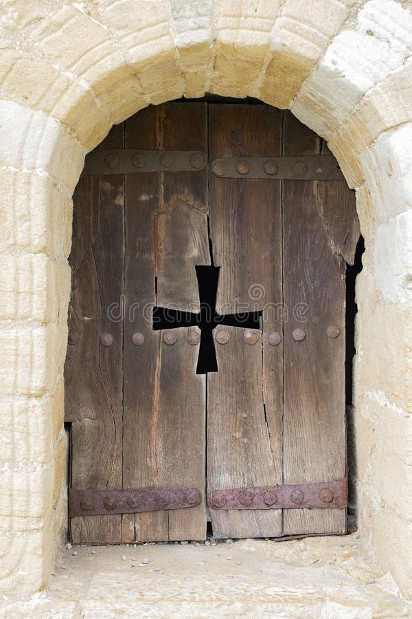 Arch window of a catholic church with wooden shutters and a carved cross. The window of the Catholic Church in the form of an arch with wooden shutters and stock image
