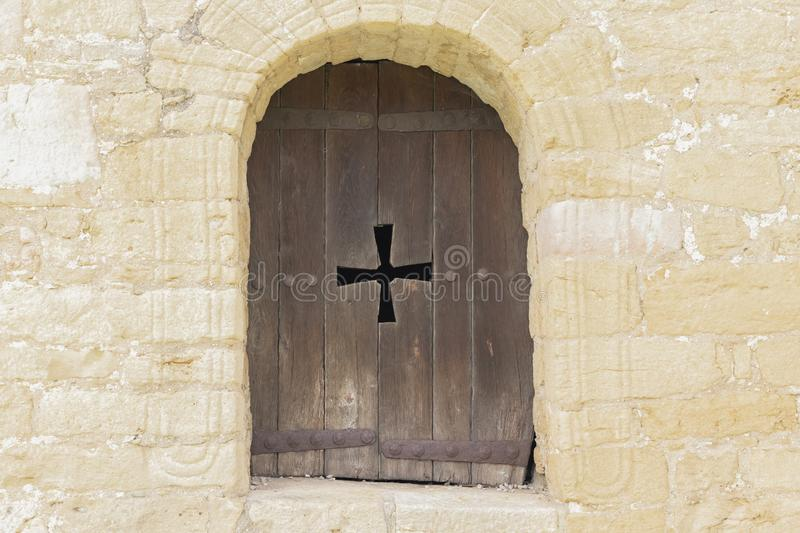 Arch window of a catholic church with wooden shutters and a carved cross. The window of the Catholic Church in the form of an arch with wooden shutters and royalty free stock images