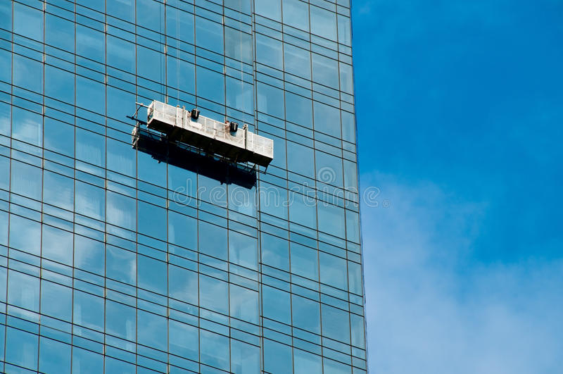 Window cleaner in a gondola cleaning the windows stock image