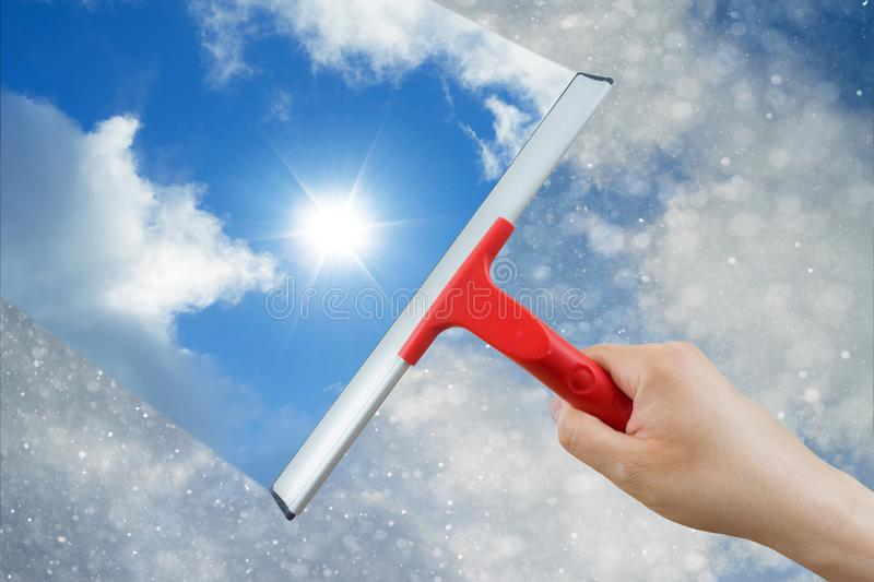 Window cleaner using a squeegee to clean the sky above stock photography