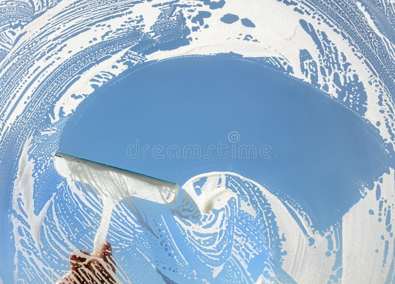 Window cleaner using a squeegee to wash a window stock image