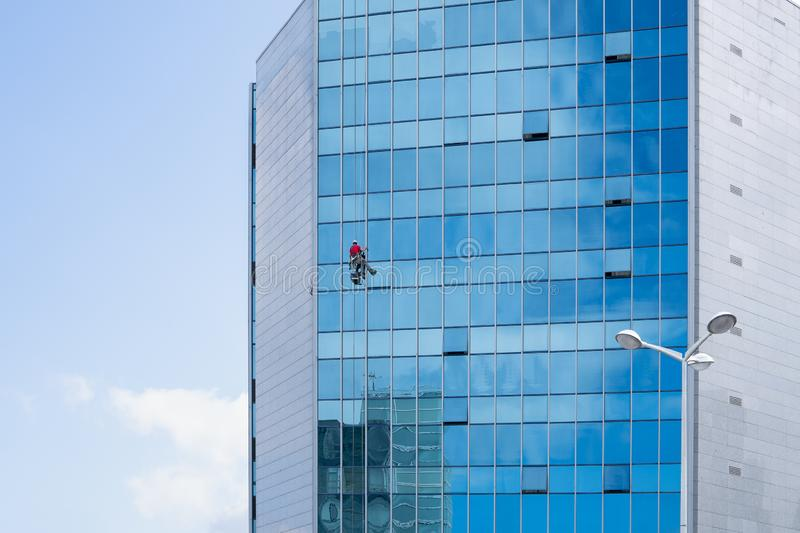 Window cleaner working on a glass facade suspended. Cleaning concept. Copy space royalty free stock photography