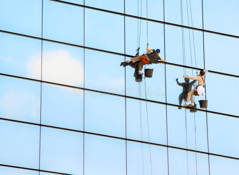 Window cleaners. Industrial mountaineering workers wash windows of a high-rise building stock photo