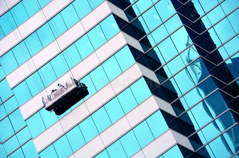 Window cleaners in gondola royalty free stock photography