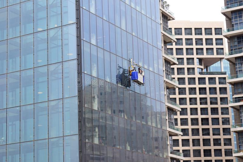 Window cleaners hanging on their basket. Working outdoor. Ramat Gan, Israel, April 2019 stock photos
