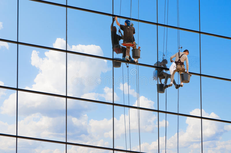 Window cleaners. Workers wash windows of a high-rise building stock photo