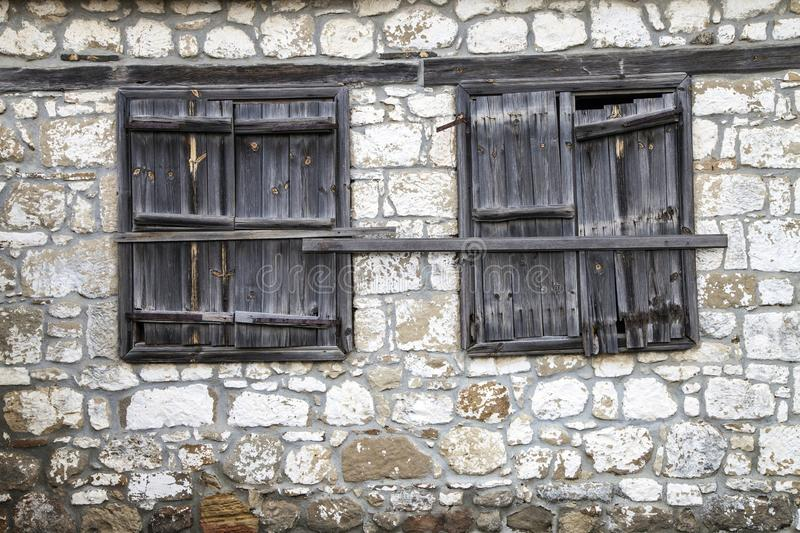 Window with closed weathered wooden shutters. On dry stone wall stock images