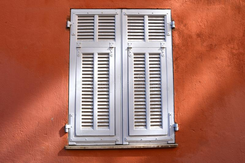 Window closed with white wooden shutters. on a red wall stock photos