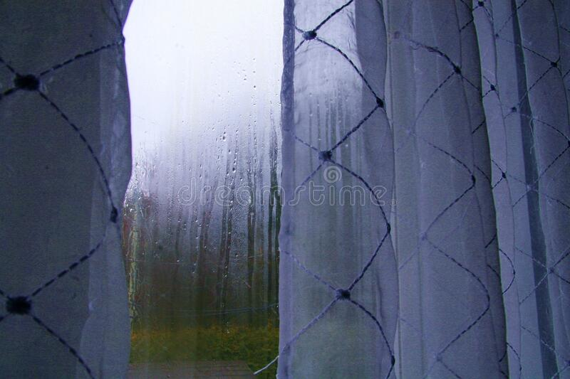 Window Cold Rainy Weather water Drops Foggy Blue Nostalgic Beauty. Curtains Window Cold Rainy Weather water Drops blue Nostalgic royalty free stock photo