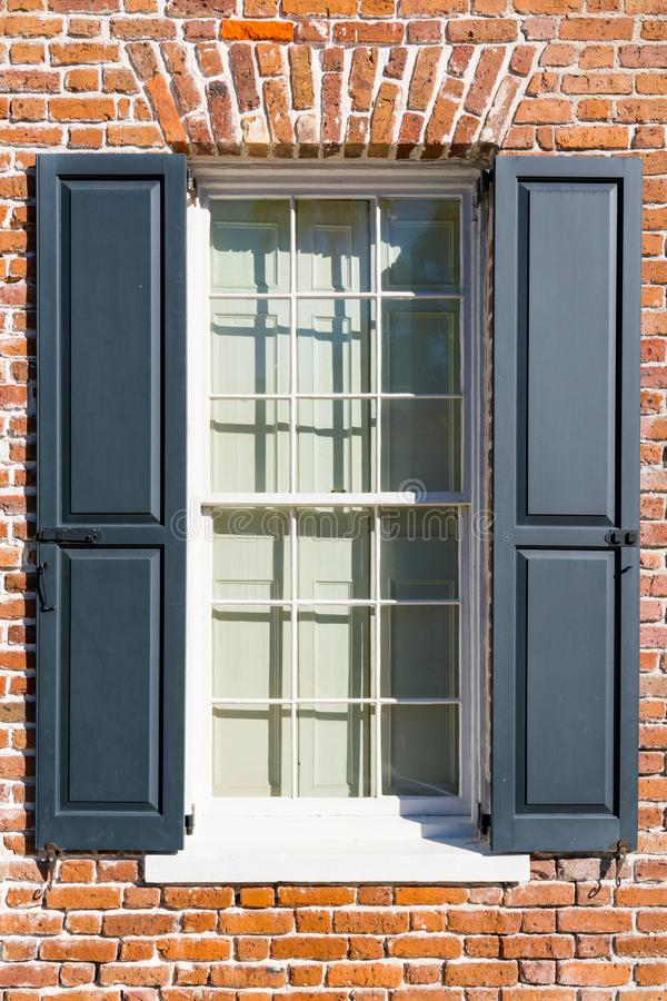 Window of Colonial Brick Home. Exterior window of colonial brick home with black shutters royalty free stock photo
