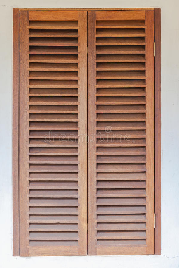 Window Wood Shutters. Window covered with solid wood shutters fiited on house stock image
